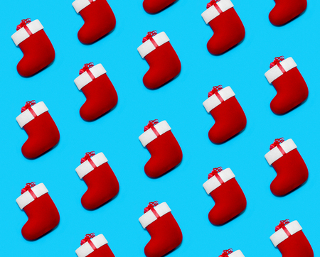 Pattern made with Christmas Red Socks on Blue Background. Creative Minimal Holiday Composition. Flat Lay 写真素材