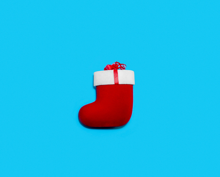Christmas Red Sock on Blue Background. Creative Minimal Holiday Composition. Flat Lay