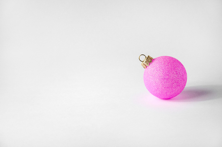 Christmas Pink Ball on Light Background. Minimal New Year Holiday Composition. Banner.  Copy Space 写真素材