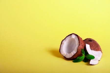 Cracked Coconut with Mint on Yellow Background. Exotic Food. Summer Tropical Concept. Copy Space For Your Text