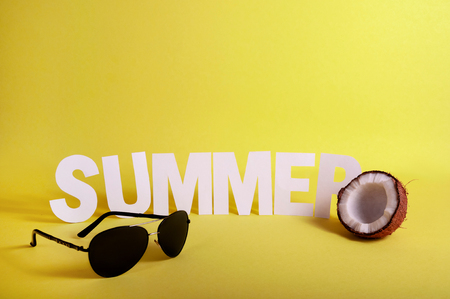 Word SUMMER made White Paper Letters with Half Coconut and glasses on Yellow Background. Copy Space For Your Text 写真素材