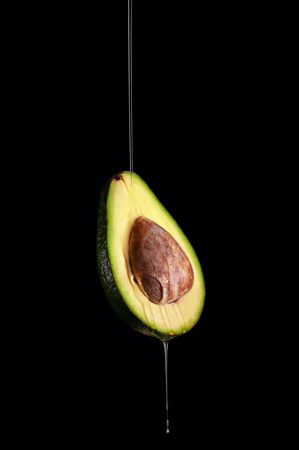 Ripe Half Avocado Levitation with Dripping Oil on Dark Background. Copy Space For Your Text