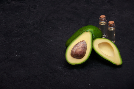 Ripe Half Avocados with Oil on Dark Stone Background. Copy Space For Your Text