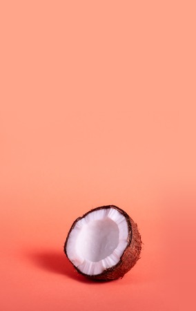 Half Coconut on Coral Background. Exotic Food. Summer Tropical Concept. Copy Space For Your Text