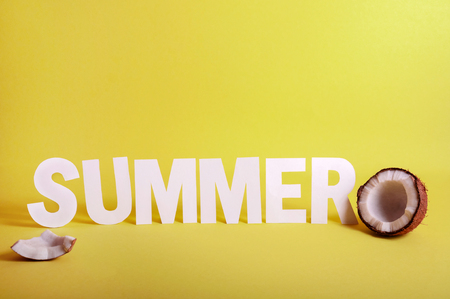 Word SUMMER made White Paper Letters with Half Coconut on Yellow Background. Copy Space For Your Text