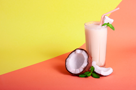 Pina Colada - Tropical Cocktail with Pineapple Juice, Coconut Milk and Rum. Fresh Summer Drink with Cracked Coconut and Mint on Coral and Yellow Background. Copy Space For Your Text