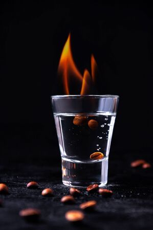 Burning Sambuca in Glass with Coffee Beans on Dark Background. Concept Shot Alcohol Cocktails