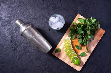 Mojito Cocktail Making. Mint, Lime, Ice, Glass and Bar Shaker on Dark Stone Table. Copy Space For Your Text