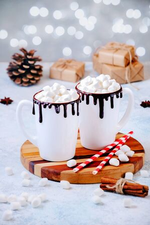 Christmas Hot Drink. White Cups of Cocoa or Chocolate with Marshmallows and Spices Cinnamon on Light Background with Christmas Decorations and Lights of Bokeh.