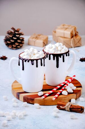 Christmas Hot Drink. White Cups of Cocoa or Chocolate with Marshmallows and Spices Cinnamon on Light Background with Christmas Decorations.
