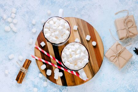 Christmas Hot Drink. White Cups of Cocoa or Chocolate with Marshmallows and Spices Cinnamon on Light Background with Christmas Decorations. Flat Lay