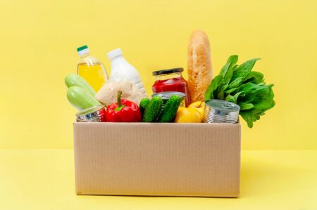 Donation Box with Supplies Food for People in Isolation on Yellow Background. Essential Goods: Oil, Canned Food, Cereals, Milk, Vegetables, Fruit.
