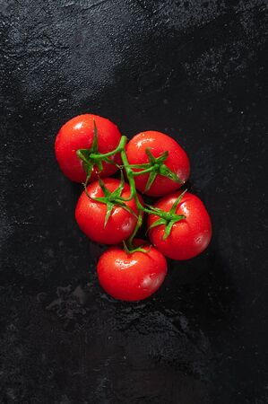 Ripe Tomatoes on Dark Stone Table. Top View. Flat Lay.