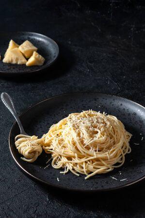 Cacio e Pepe - Italian Pasta with Cheese and Pepper on Black Plate on Dark Background