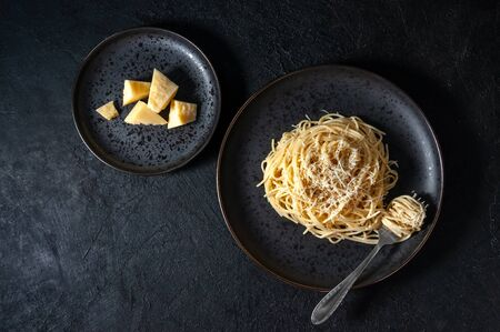 Cacio e Pepe - Italian Pasta with Cheese and Pepper on Black Plate on Dark Background. Top View Flat Lay. Copy Space