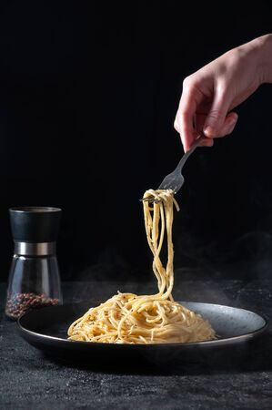 Cacio e Pepe - Hot Italian Pasta with Cheese and Pepper on Black Plate, Woman Holding Fork Spaghetti on Dark Background