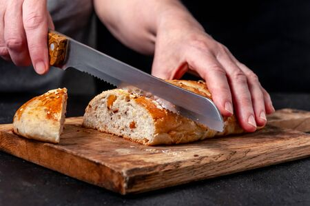 Woman Slices Homemade Wholemeal Multigrain Bread with Flax Seeds and Sesame on Wooden Board on Dark Table