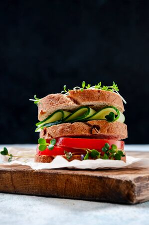 Homemade Healthy Sandwich with Wholegrain Bread, Cucumber, Tomato and Micro Herbs Watercress Salad on Wooden Board.