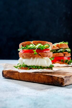 Homemade Healthy Sandwich with Wholegrain Bread, Poached Egg, Cucumber, Tomato and Micro Herbs Watercress Salad on Wooden Board.