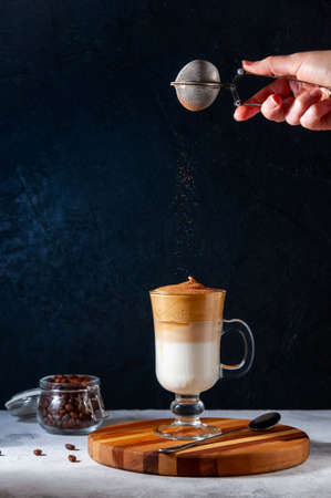 Iced Dalgona Coffee with Sifting Cocoa on Light Grey and Dark Background. Trendy Creamy Whipped Coffee. South Korean Cold Summer Drink.