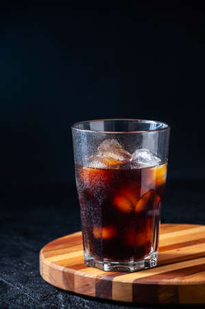 Iced Cola or Cold Coffee in Tall Glass on Dark Background. Concept Refreshing Summer Drink. Banque d'images