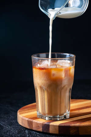Milk Being Poured into Iced Coffee in Tall Glass on Dark Background. Concept Refreshing Summer Drink.