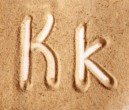 Letter K. English Handwritten Alphabet In The Sand. Banque d'images