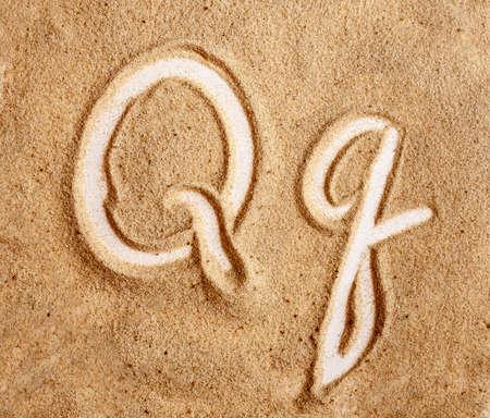 Letter Q. English Handwritten Alphabet In The Sand.