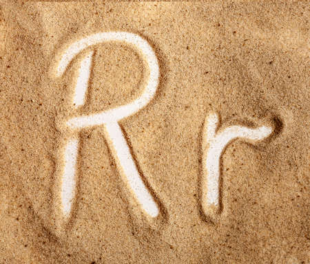 Letter R. English Handwritten Alphabet In The Sand. Banque d'images