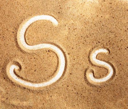 Letter S. English Handwritten Alphabet In The Sand.