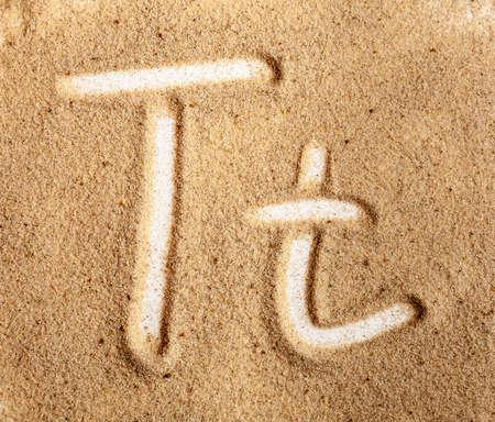 Letter T. English Handwritten Alphabet In The Sand.