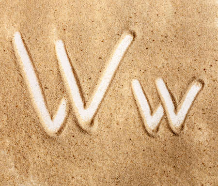 Letter W. English Handwritten Alphabet In The Sand.