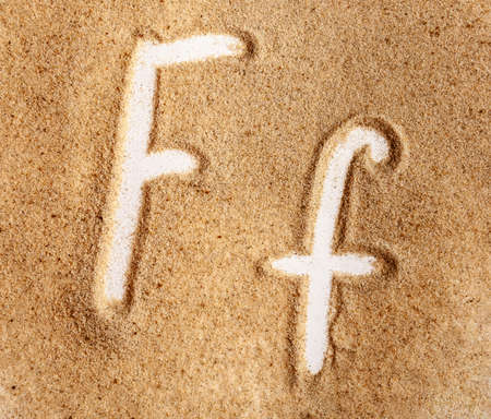 Letter F. English Handwritten Alphabet In The Sand. Banque d'images