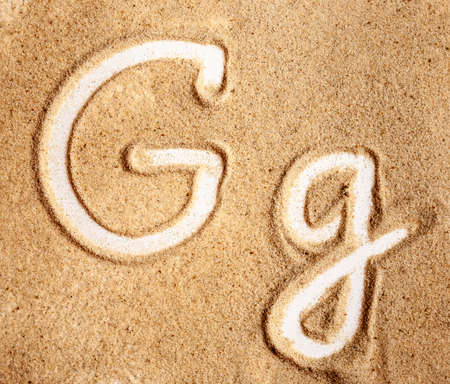 Letter G. English Handwritten Alphabet In The Sand.