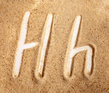 Letter H. English Handwritten Alphabet In The Sand. Banque d'images