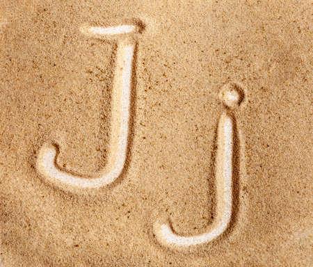 Letter J. English Handwritten Alphabet In The Sand.