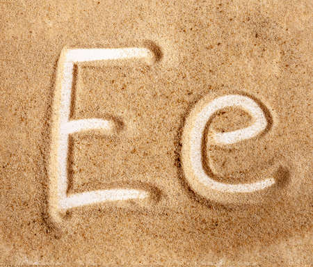 Letter E. English Handwritten Alphabet In The Sand. Banque d'images