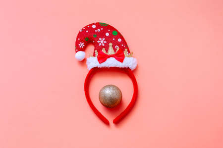 Decorative Portrait with Santa Hat and Christmas Ball on Pink Background. Creative Minimal Christmas Concept