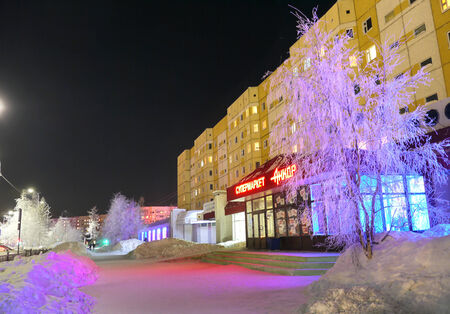 NADYM, RUSSIA - FEBRUARY 25, 2013: Supermarket in the center of the city in Nadym, Russia - February 25, 2013. Beautifully illuminated building and trees. Far north, Nadym.