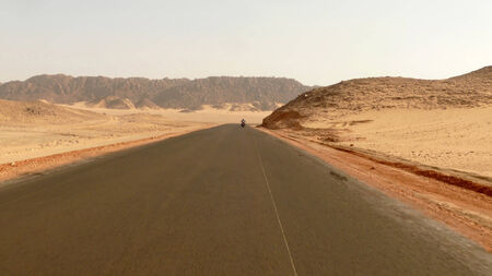 Africa. The road running through the Sahara desert. Unknown man riding a motorcycle on the road. photo