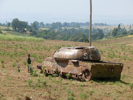 old times: JIGA, ETIOP�A - 24 de noviembre de 2008: El tanque sovi�tico en los viejos tiempos. Ni�o desconocido de pie cerca del tanque. Paisaje de la naturaleza, la vegetaci�n en el valle.