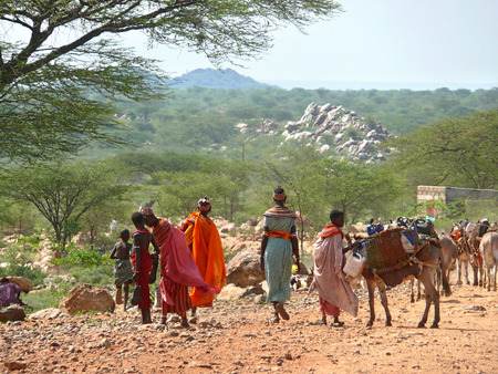ISIOLO, KENYA - NOVEMBER 28, 2008: Strange women of the tribe Tsonga carry water in bottles on donkeys in Isiolo, Kenya - November 28, 2008. Donkeys laden with baggage. Landscape of mountains in the background. Stock Photo - 27170777