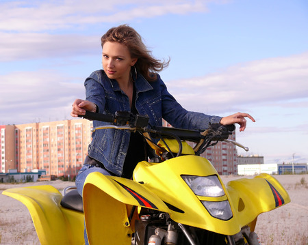 helen: Beautiful blonde on sport quadrocycle on background of the city Nadym.