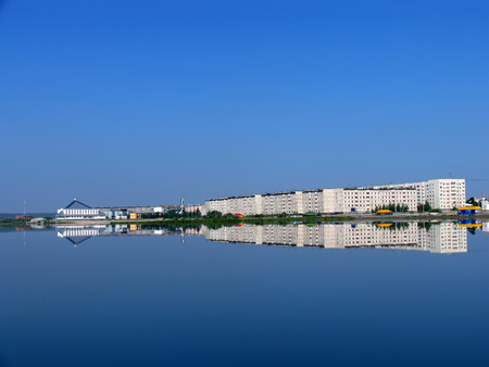 reflectivity: Nadym, Russia - July 20, 2004: panorama of the city on the river Nadym in Nadym, Russia - July 20, 2004. Reflection of the city in water. Editorial