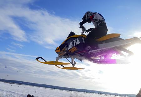 springboard: Nadim, Rusia - 28 de febrero de 2009: Snoukross. Vadim Vasuhin en salto con trampol�n en moto de nieve durante la nieve carrera a campo traviesa.
