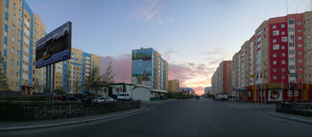 Nadym, Russia - June 20, 2008: the City skyline in Nadym, Russia - June 20, 2008. City Central road with riding on her car. Sunset over the city.