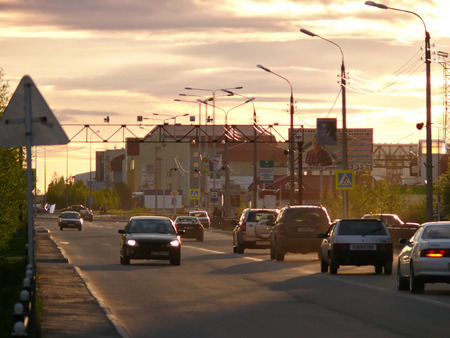 Nadym, Russia - June 26, 2008: the City skyline in Nadym, Russia - June 26, 2008. City Central road with riding on her car. Sunset over the city.