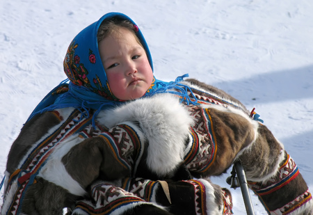 herder: Nadym, Russia - March 18, 2006: the national holiday, the day of the reindeer herder in Nadym, Russia - March 18, 2006. Unknown girl in the Nenets woman on a sledge.