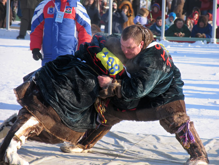 unknown men: NADYM, RUSSIA - March 2, 2007: National Holiday - Day of the reindeer herders. The wrestling unknown men on holiday in Nadym, Russia - March 2, 2007. Editorial