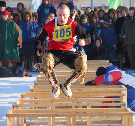 Nadym, Russia - March 2, 2007: the national holiday - the Day of the reindeer herder in Nadym, Russia - March 2, 2007. Sports competitions. Unknown man jumps over obstacles.